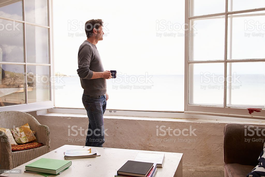 Man Standing At Window And Looking At Beautiful Beach View stock photo