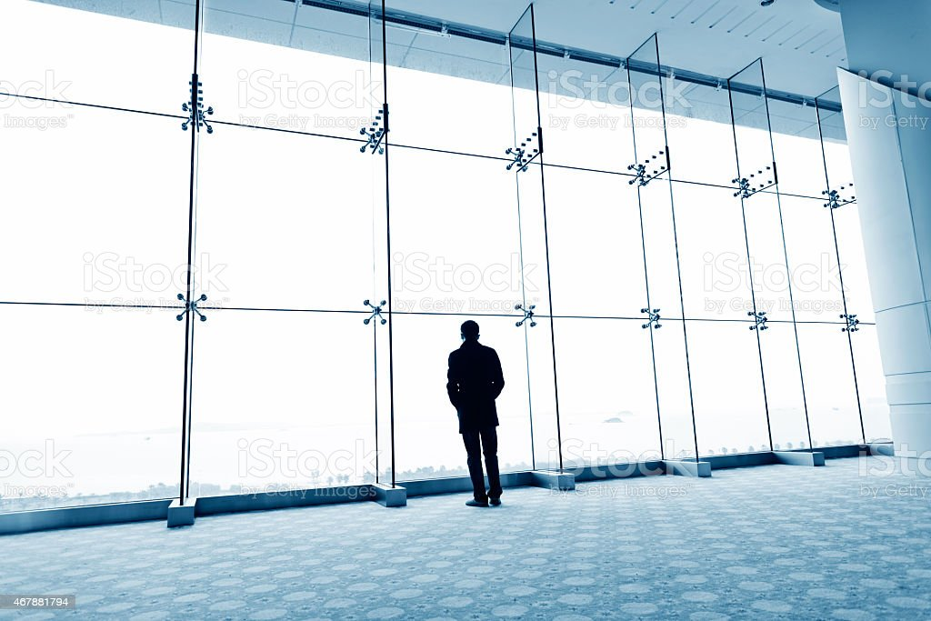 Man standing before large windows looking out stock photo