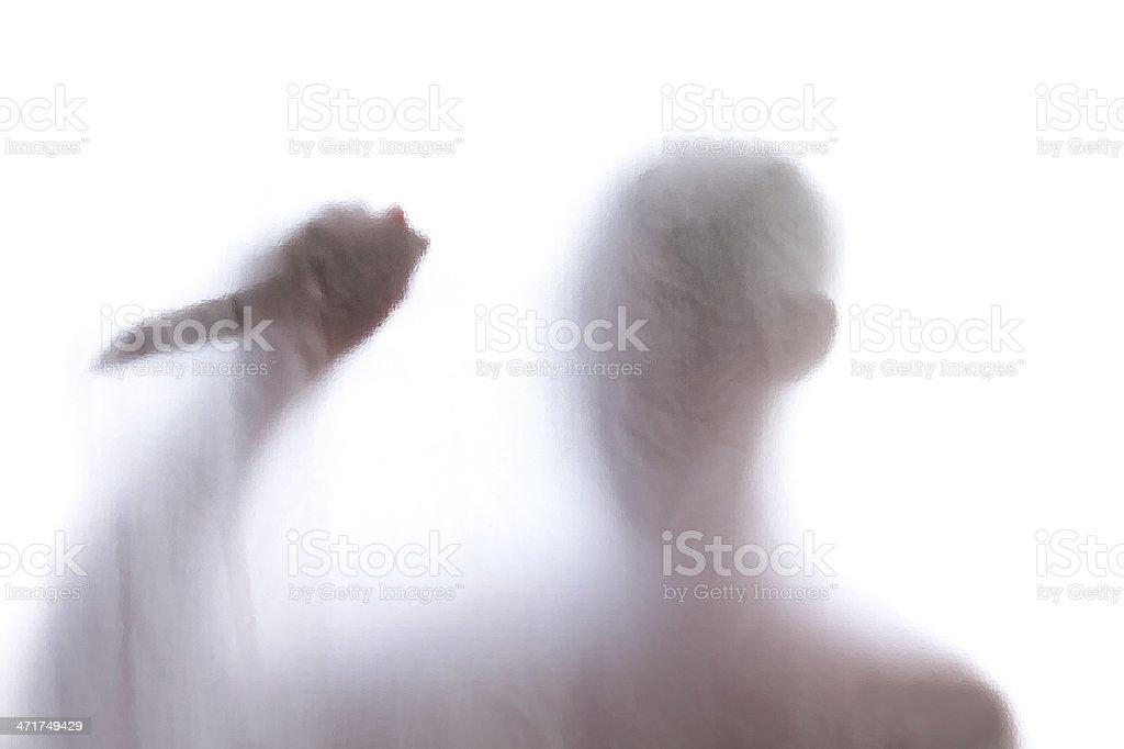 Man standing behind frosted glass and holding a knife royalty-free stock photo