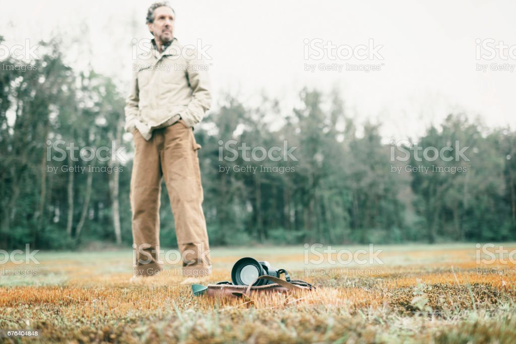 Man standing behind leather bag with camera lying in field. stock photo