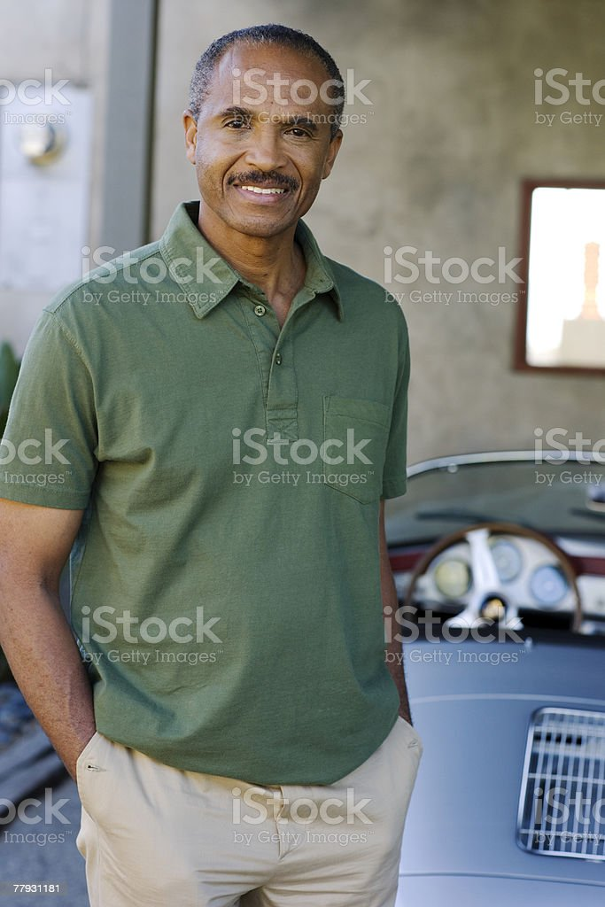 Man standing behind parked convertible car royalty-free stock photo