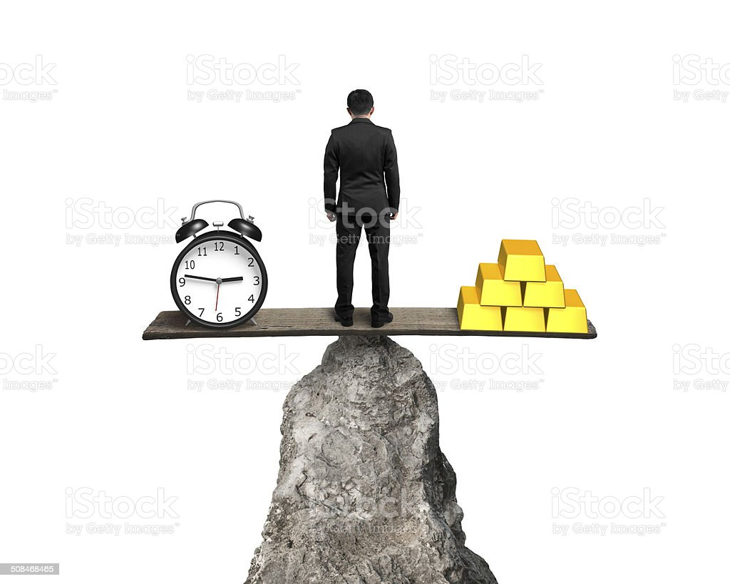 man standing between clock and gold balancing on rock seesaw stock photo