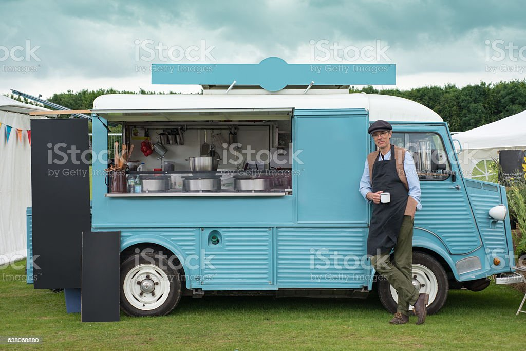 Man Standing by a Blue Food Truck stock photo