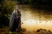 Man standing by a lake outdoors in costume