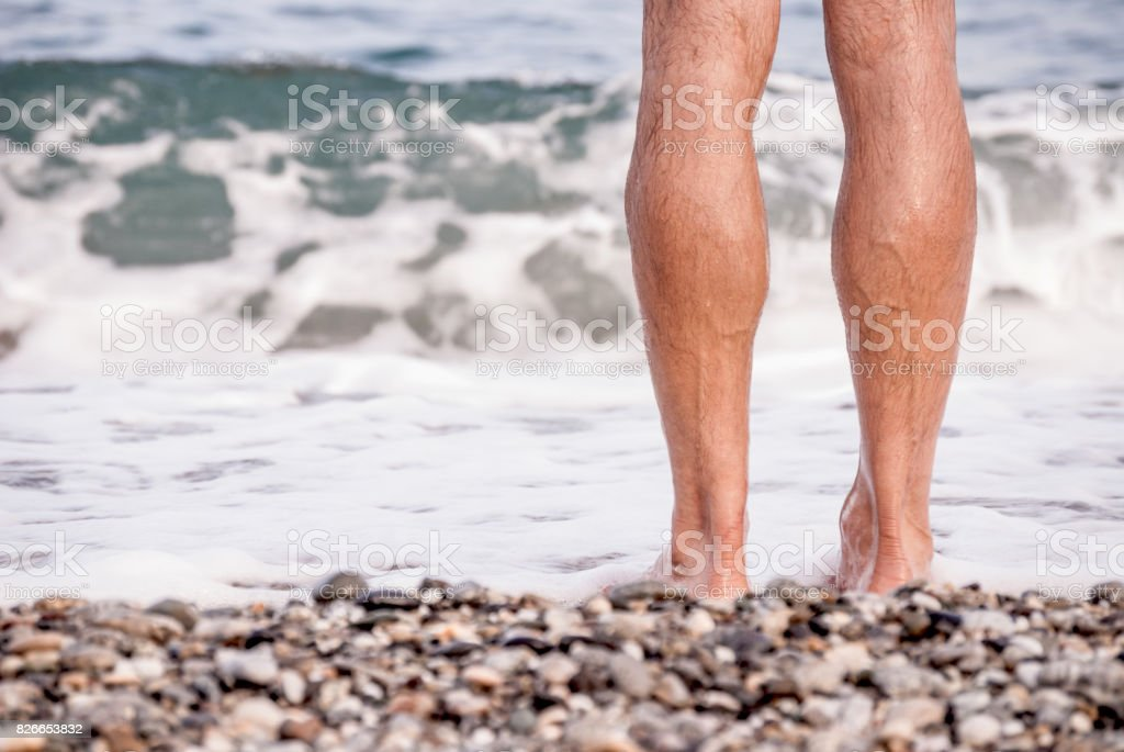Man Standing by the Sea - Legs Close-Up stock photo
