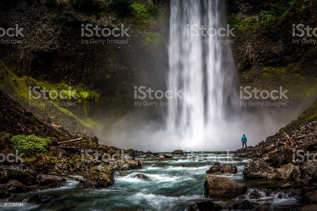 Man standing close to huge waterfall. stock photo