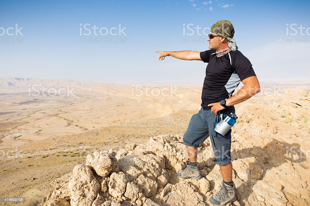 Man standing desert mountain cliff edge. stock photo