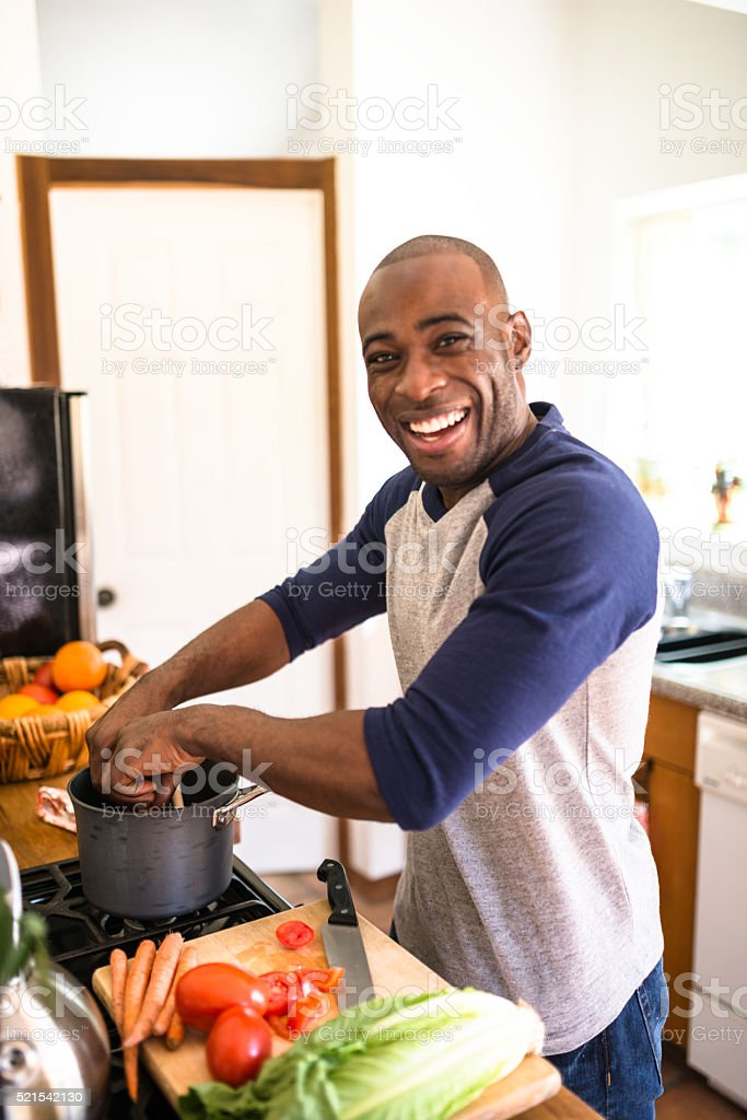 man standing happiness on the kitchen and preparing food stock photo