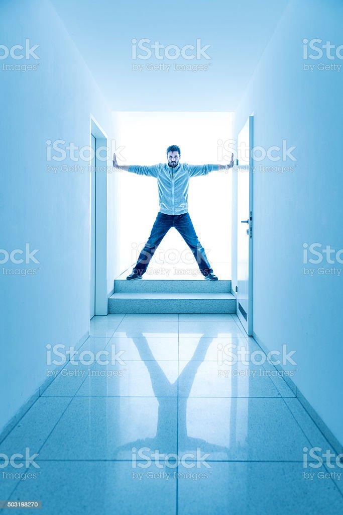 man standing in a bright corridor stock photo