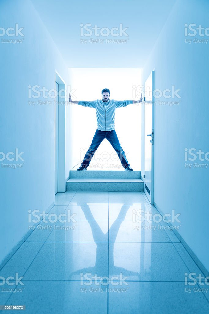 man standing in a bright corridor stock photo