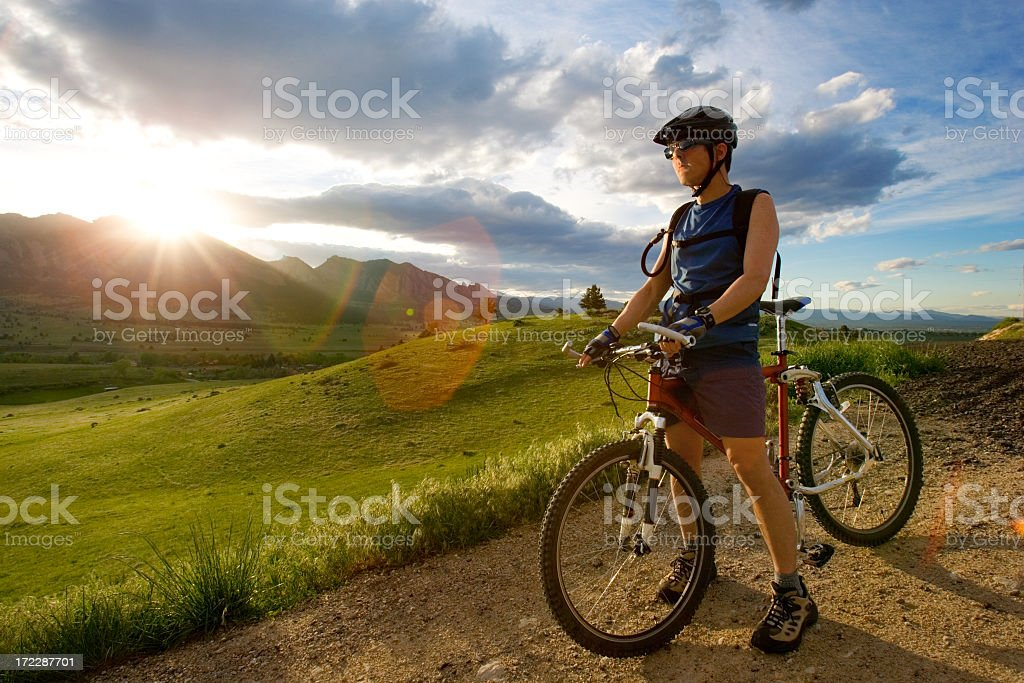 A man standing in a dirt road with a bike stock photo