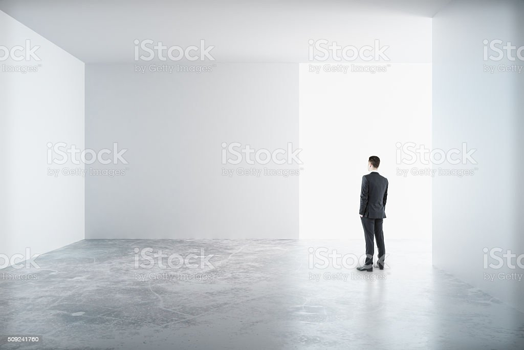 Man standing in a white room stock photo