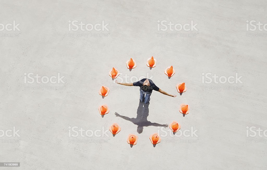 Man standing in circle of traffic cones with arms up royalty-free stock photo