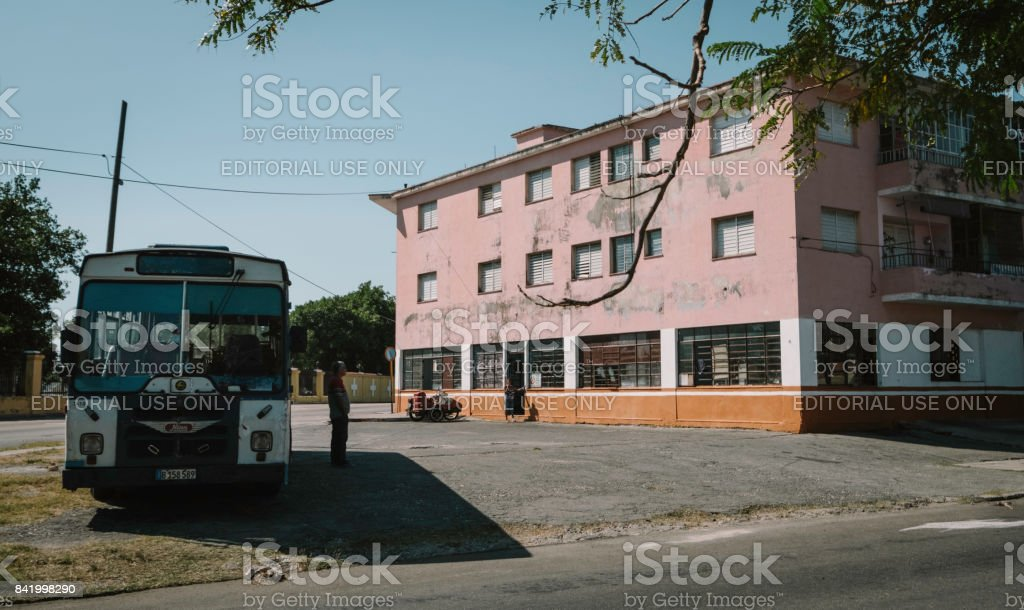 man standing in front of a broken down bus with woman and pink building in background stock photo