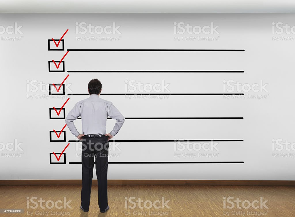 Man standing in front of a checklist with checkmarks in red royalty-free stock photo