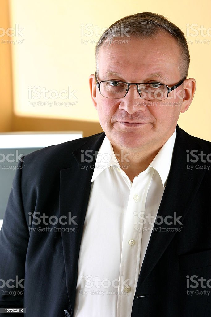 Man standing in front of a desk stock photo