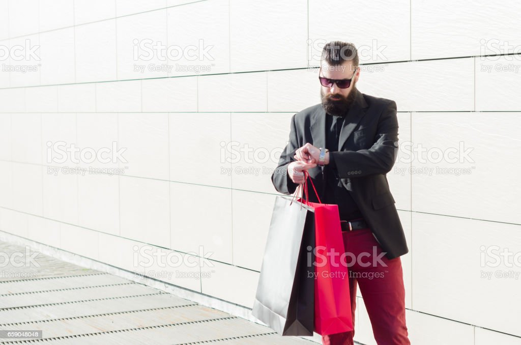 man standing in front of a shopping mall, looking at the clock and waiting for the opening shops stock photo