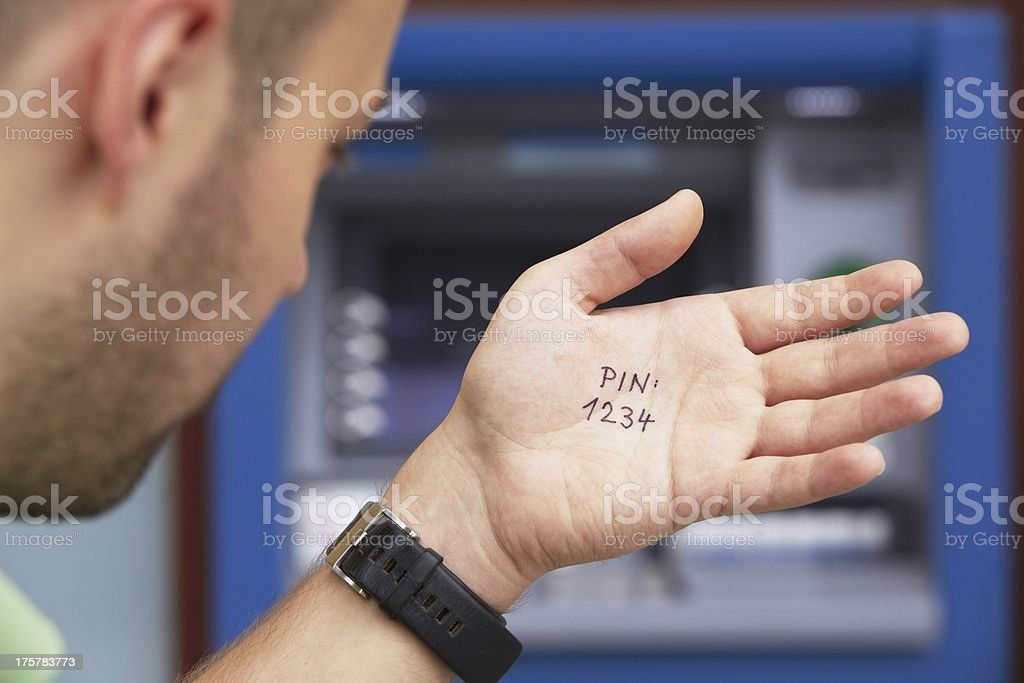 Man standing in front of an atm with a pin code on his hand stock photo