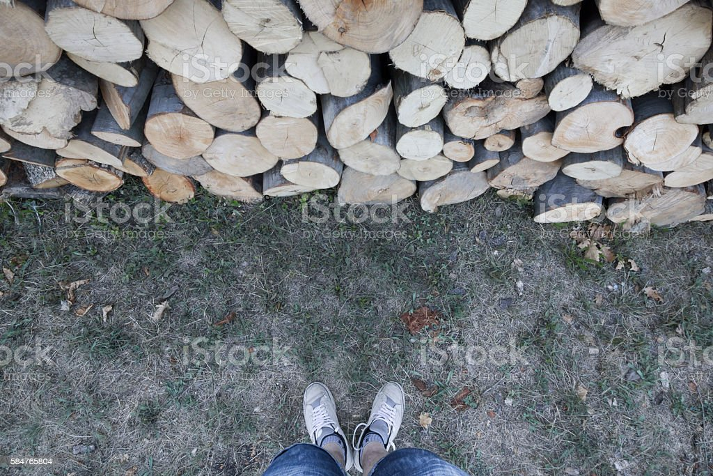 Man standing in front of chopped pile of firewoods stock photo