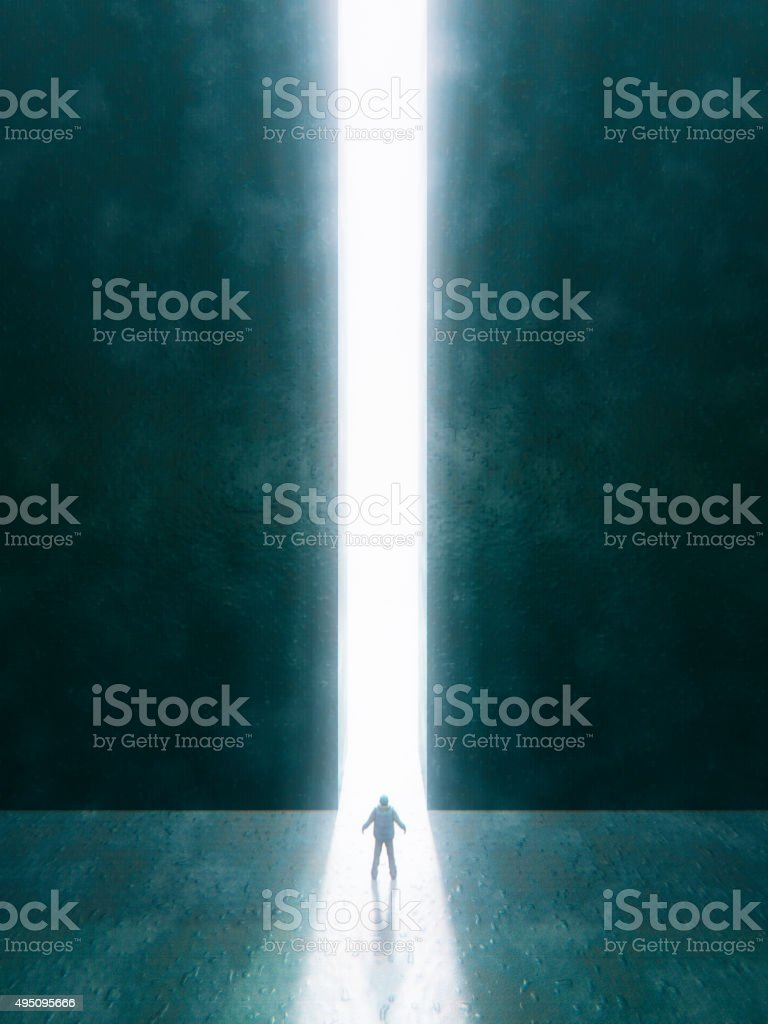 Man standing in front of mysterious bright passage stock photo
