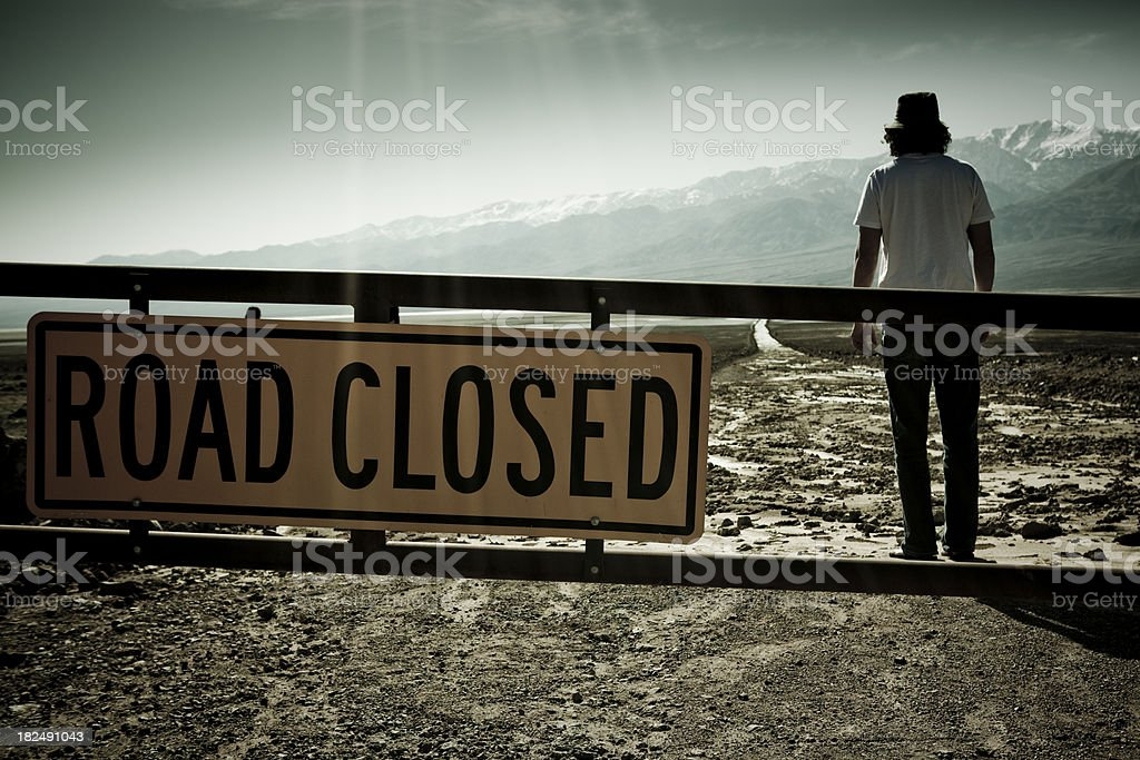 Man standing in front of Road Closed sign stock photo