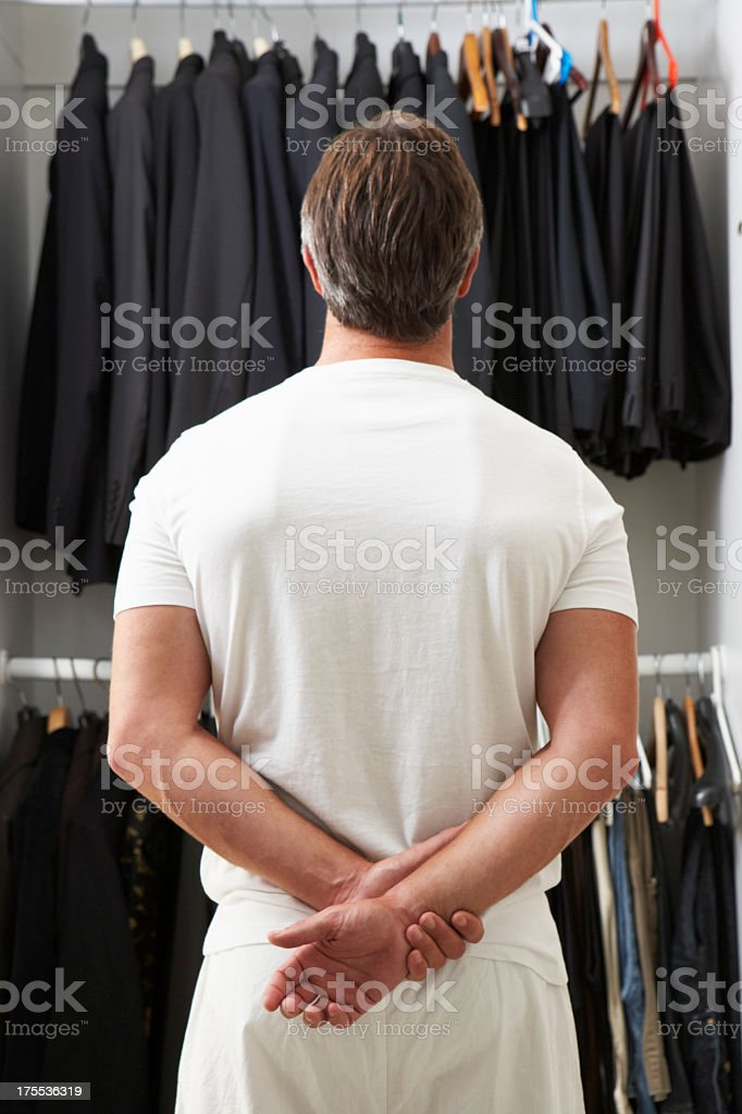 Man Standing In Front Of Wardrobe Choosing Clothes stock photo