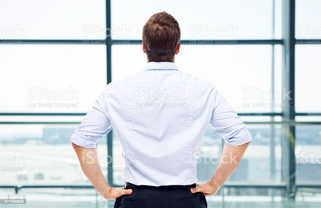 man standing in front of window at airport stock photo