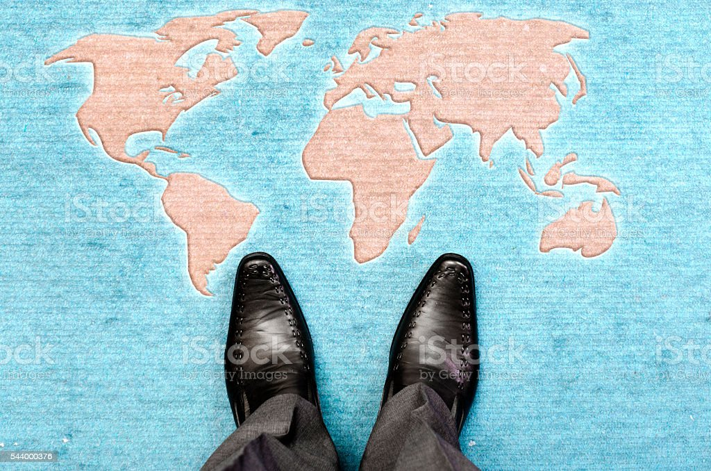 Man standing in front of world map stock photo