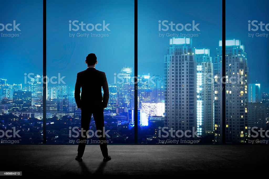 Man standing in his office looking at the city stock photo