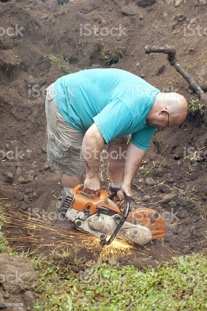 Man standing in hole, sawing old oil tank royalty-free stock photo