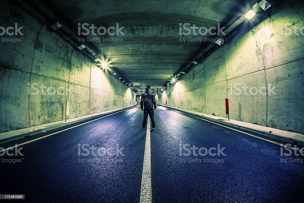 Man Standing in Middle of Underground Road Tunnel royalty-free stock photo