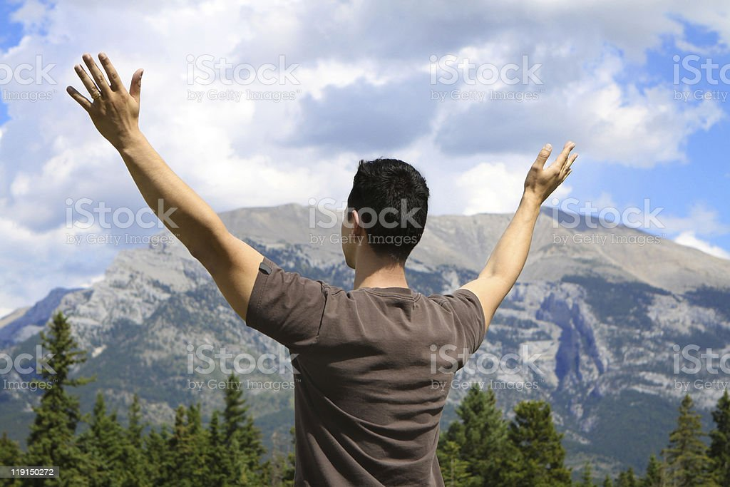 Man standing in nature with arms lifted up royalty-free stock photo