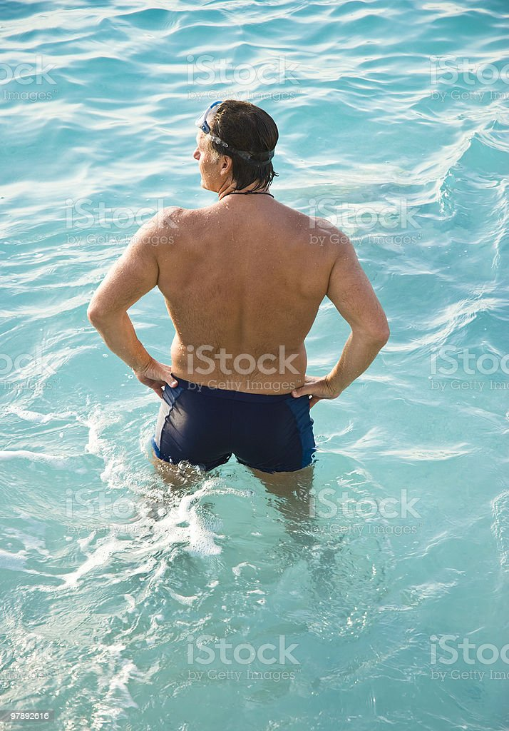 man standing in turquoise water stock photo