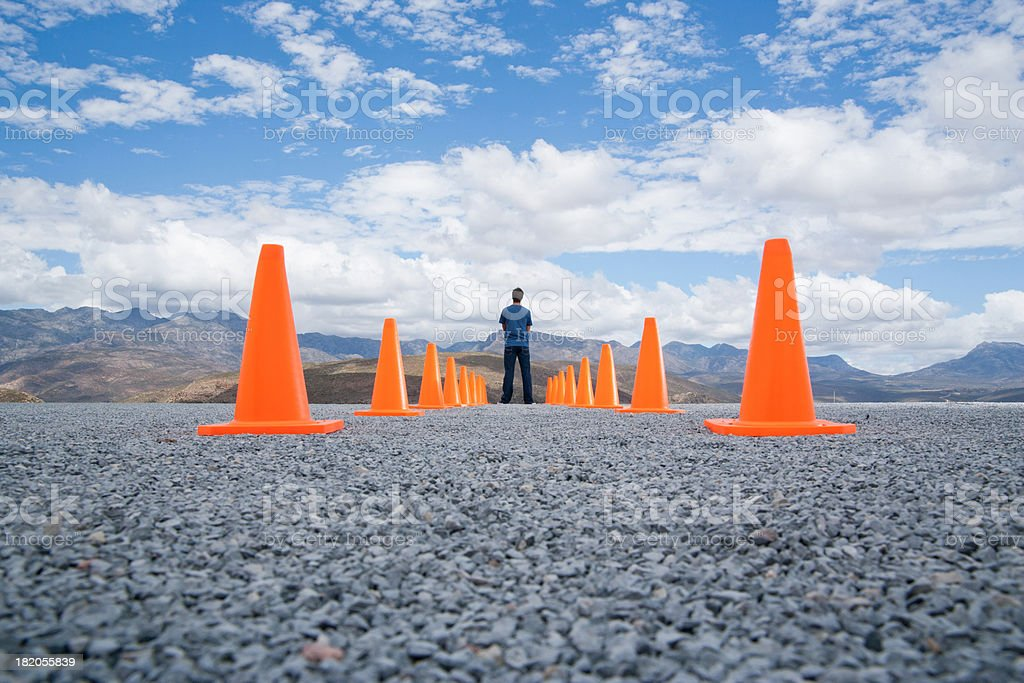 Man standing in-between two rows of safety cones stock photo