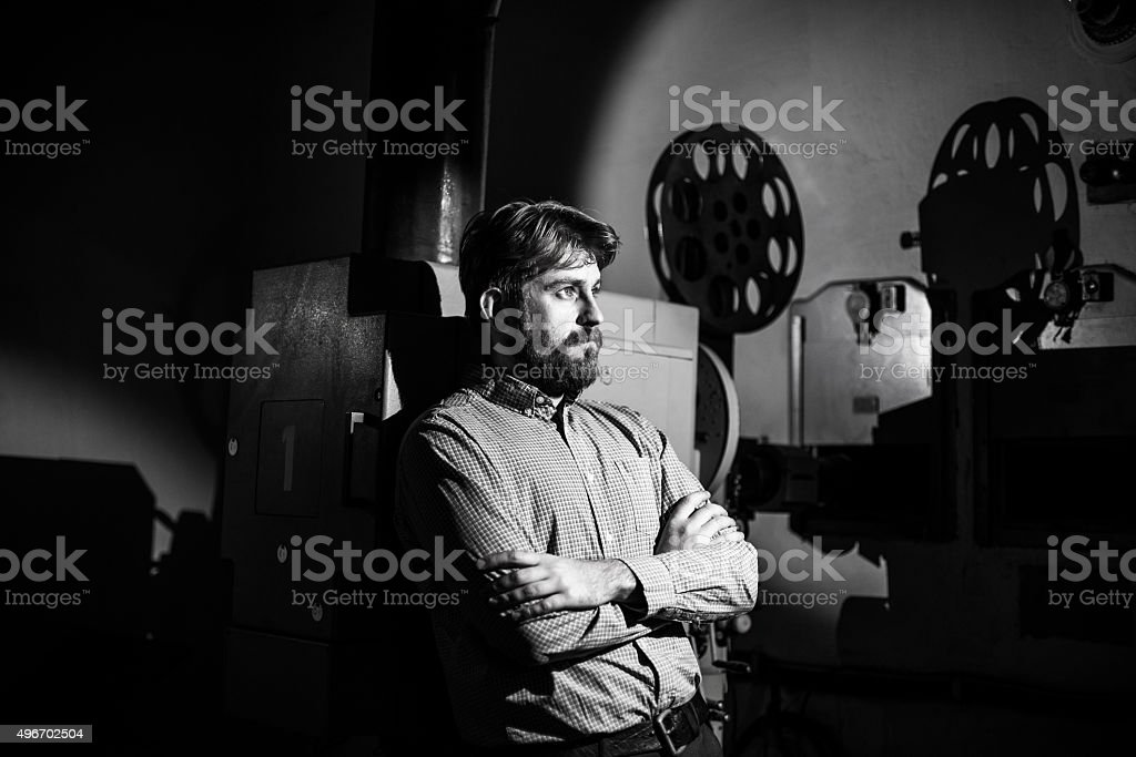 man standing near a film projector in the room projectionist stock photo