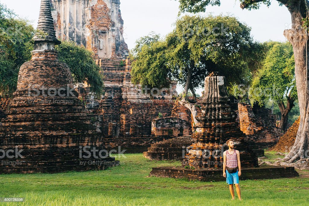 Man standing near ancient Buddhist Temples stock photo
