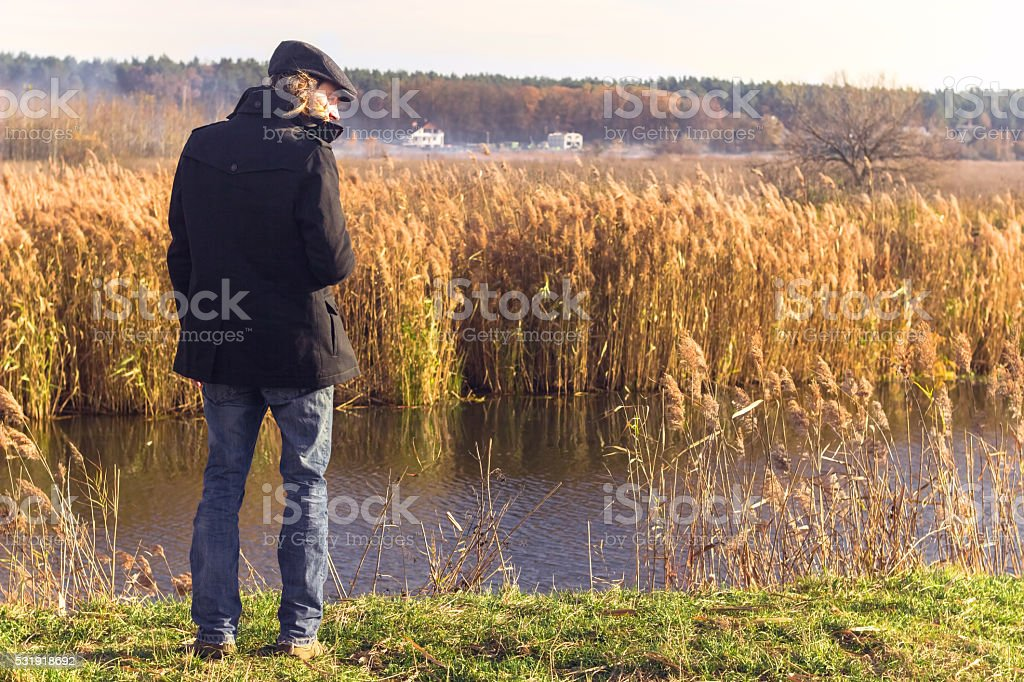 man standing near by the river, thinking about life stock photo