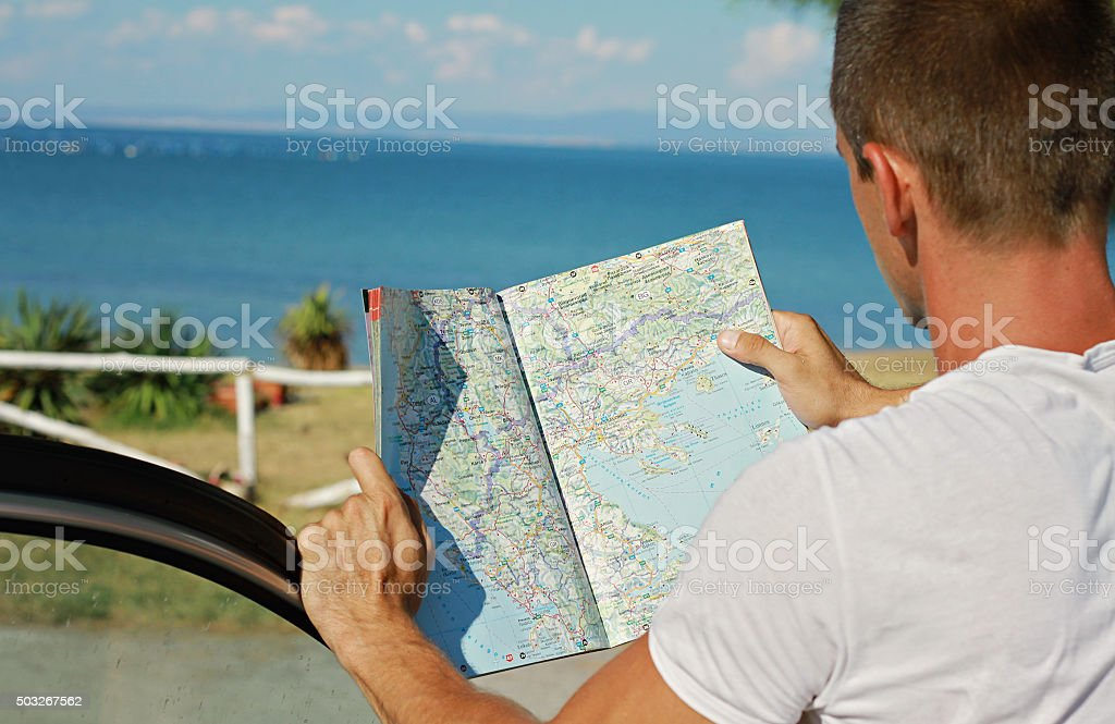 Man standing near the car and looking at road map. stock photo