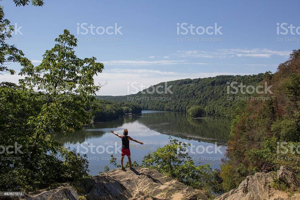 Man standing next to cliff admiring the lanscape stock photo