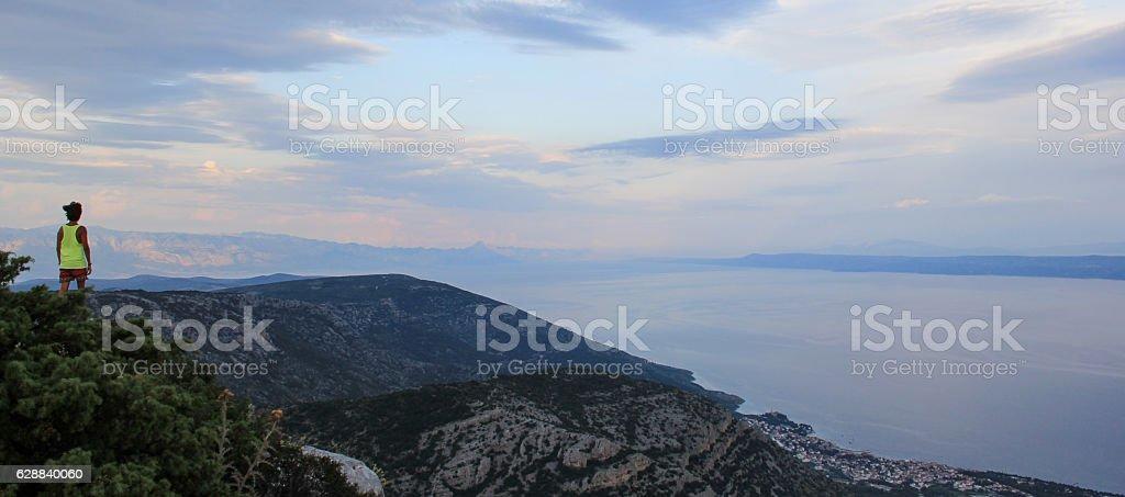 Man standing next to cliff using yellow tank in Croatia stock photo