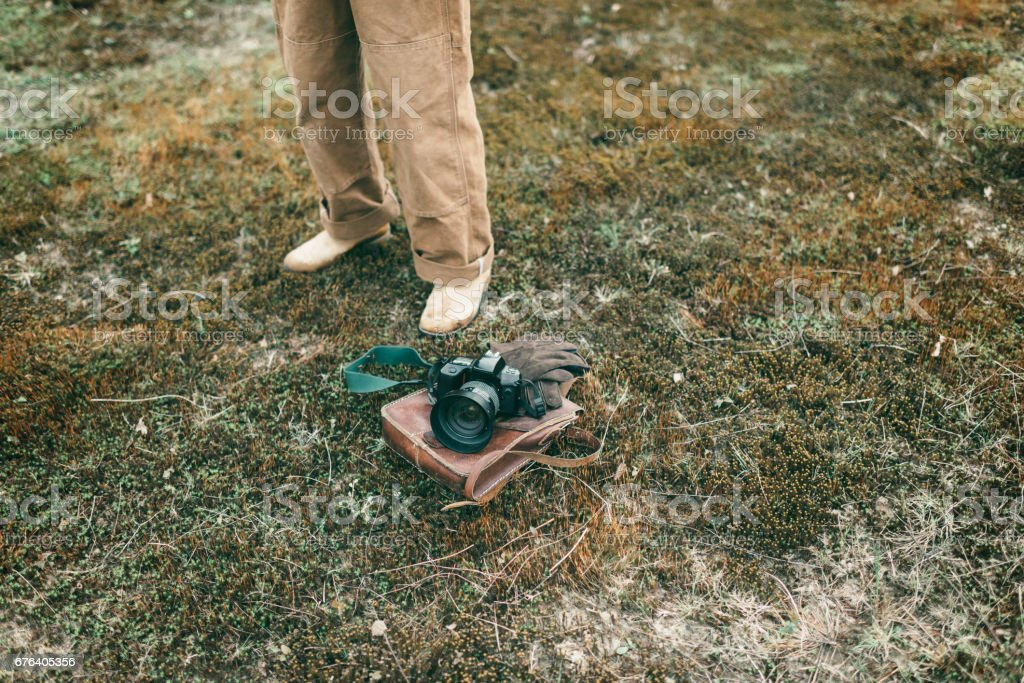 Man standing next to leather bag with gloves and camera lying in field. High angle view. stock photo