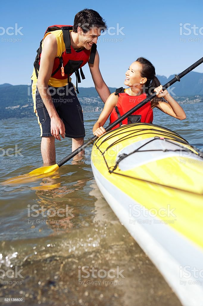 Man standing next to woman in kayak stock photo