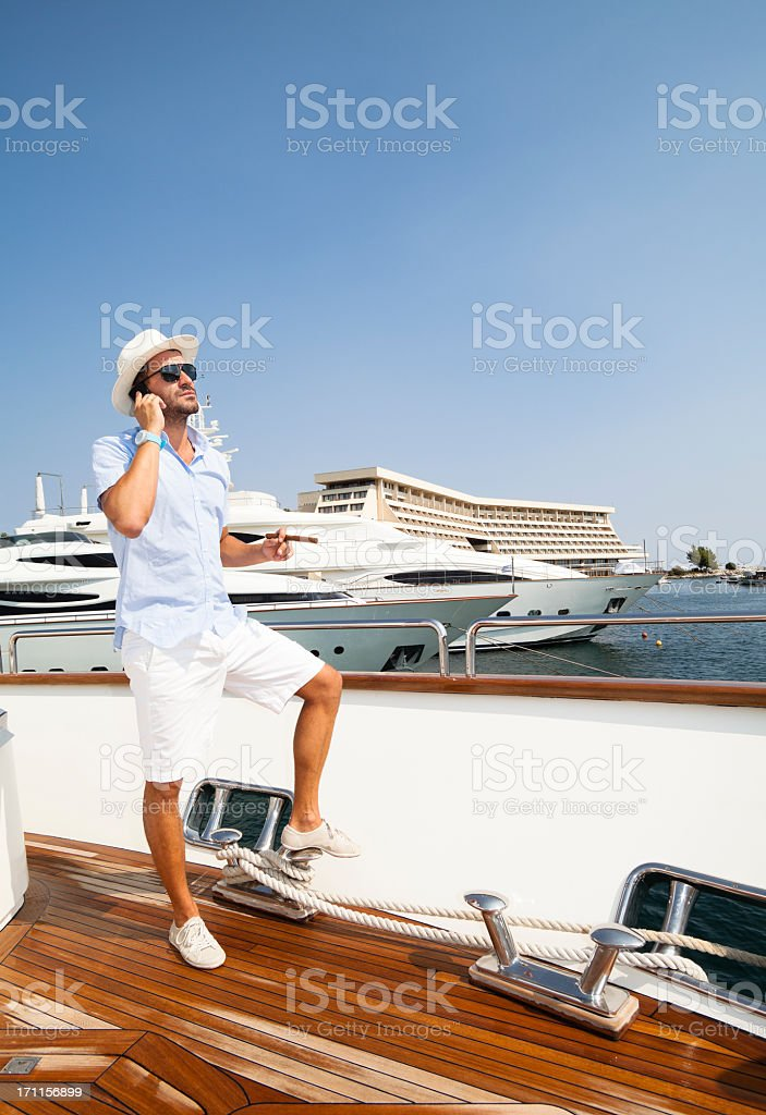 Man standing on a docked boat and talking on the phone stock photo