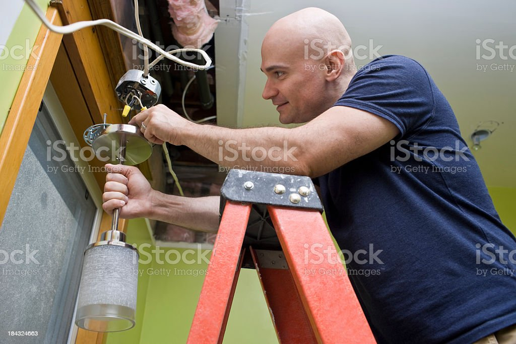 Man standing on a ladder and putting up a light stock photo