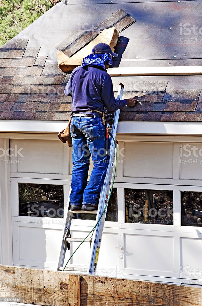 man standing on a ladder working on a damaged roof royalty-free stock photo