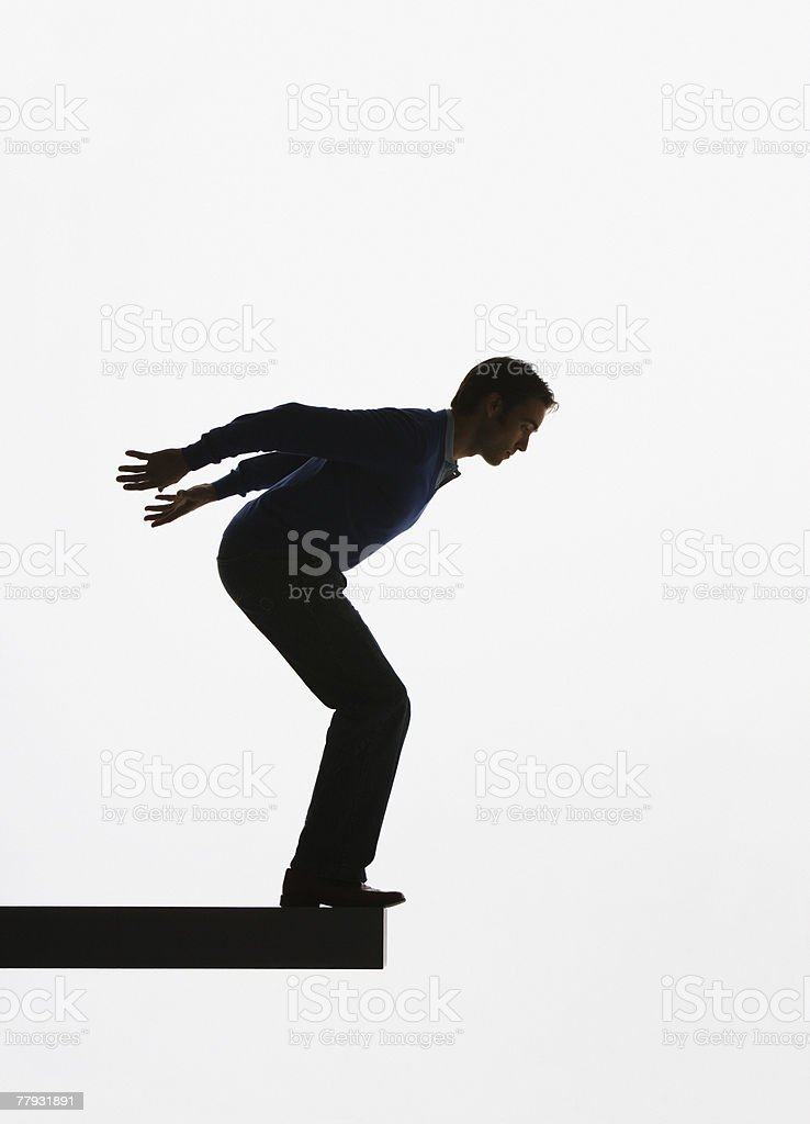 Man standing on a plank about to jump over ledge stock photo