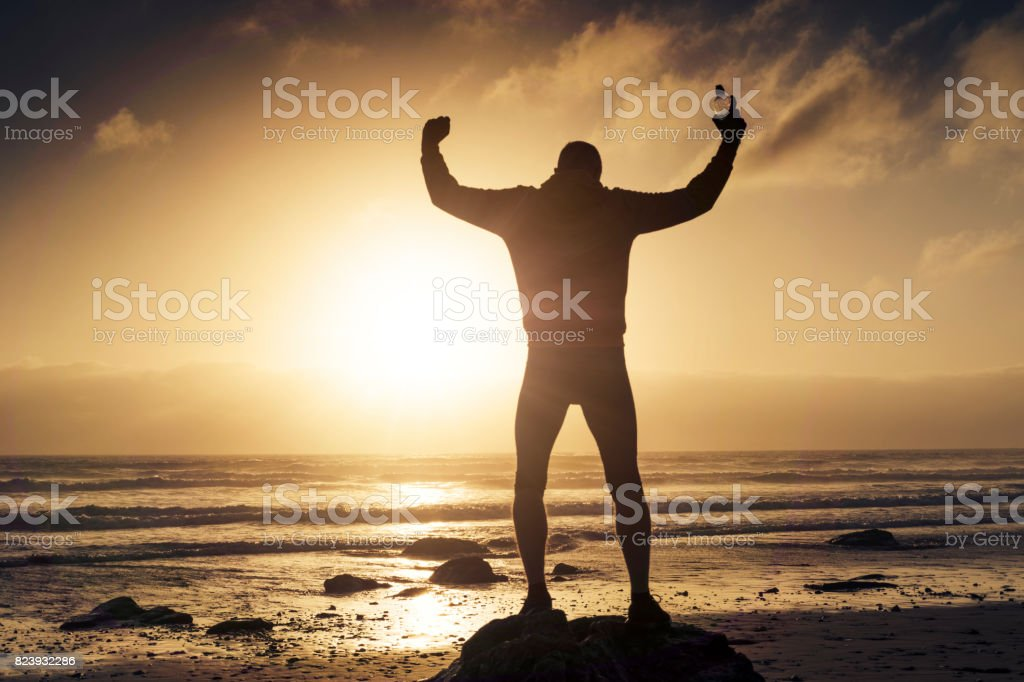 Man standing on a rock in a victory Pose after a run along a Beach. stock photo