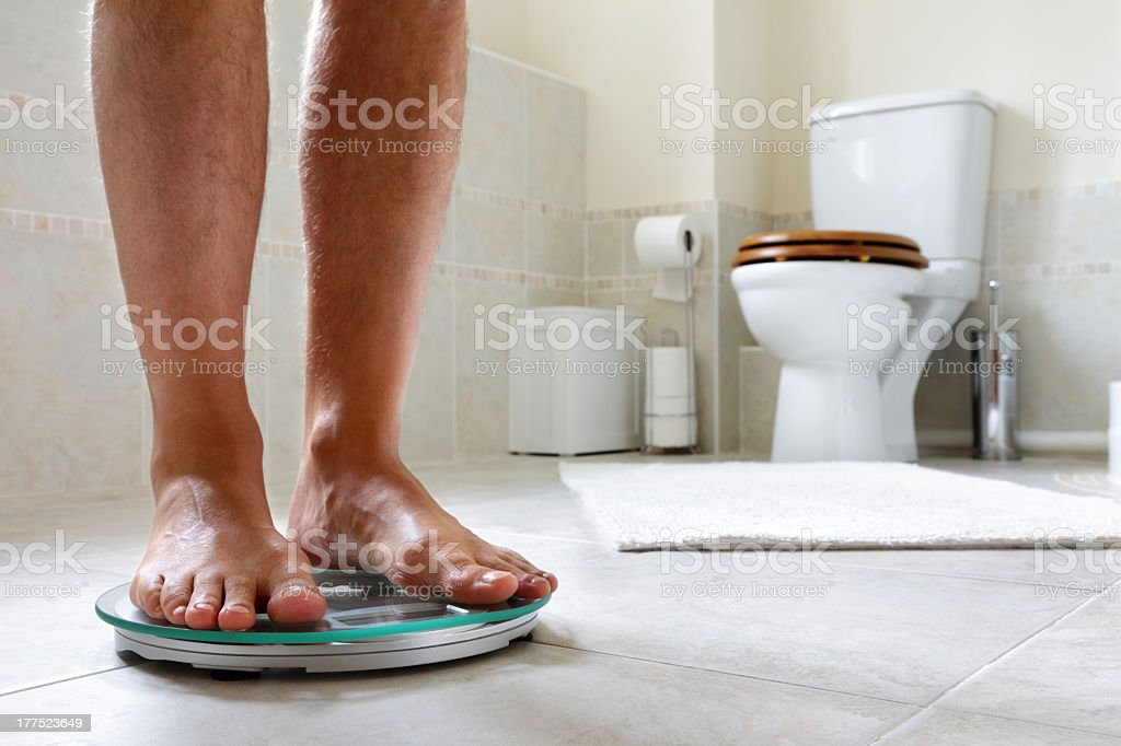Man standing on a weighing scale in the bathroom stock photo