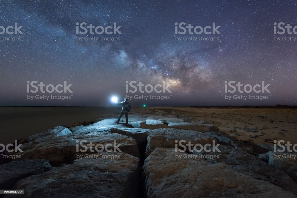 Man standing on Barnegat Jetty watching the Milky Way stock photo