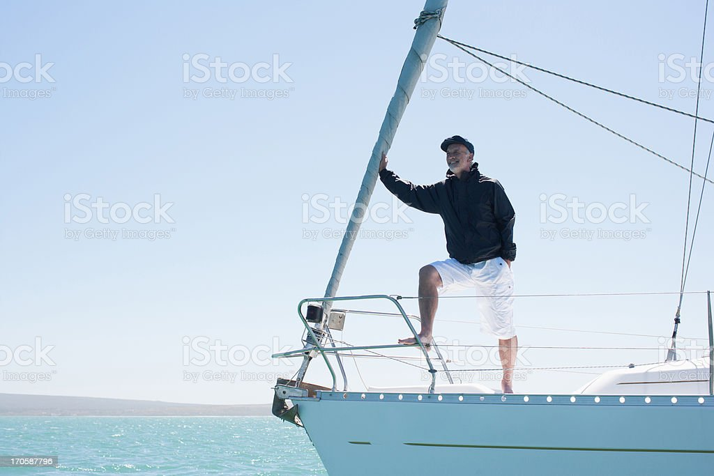 Man standing on deck of sailboat royalty-free stock photo